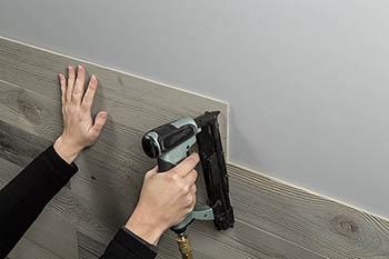 Nail planks to wall